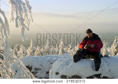 the hiker sitting on a backpack at the top of the rock in winter rests pouring himself a tea from a thermos