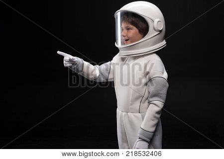 Look here. Side view of surprised cute small cosmonaut is standing in helmet and specialized protective suit and pointing finger while looking aside with curiosity and smile. Isolated background