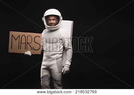Hitchhike to planet. Portrait of spaceman wearing helmet with full armor is standing and looking at camera with smile. He is holding mars sign. Isolated background with copy space in the right side