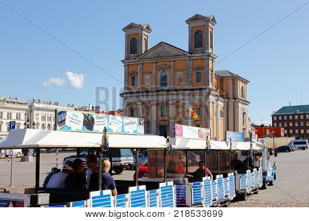 Karlskrona Sweden - August 23 2017: A Dotto train with three carriages in front of the Fredrik church at the main square.