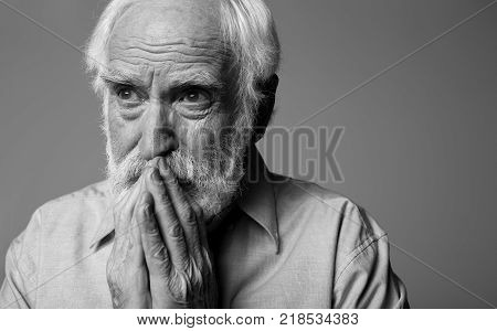 Close up portrait of dramatic pensioner looking aside while standing. He is closing mouth with wrinkled hands. Isolated on grey background and copy space