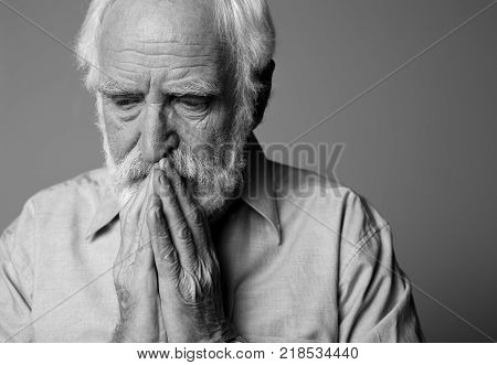 Close up portrait of dramatic pensioner expressing pain and grief. Isolated on grey background and copy space