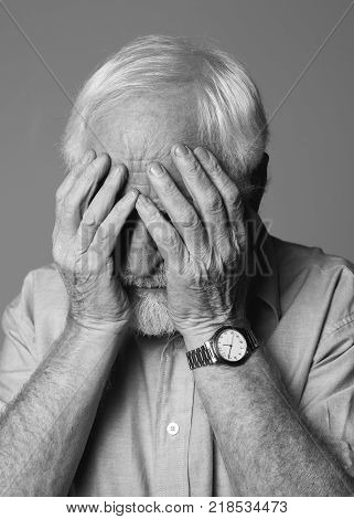Black-and-white portrait of old sad pensioner expressing stress and sorrow while standing. Isolated on grey background