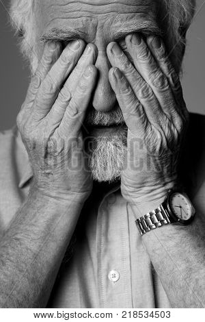 Close up portrait of sad pensioner expressing depression while standing. He is closing face with palms
