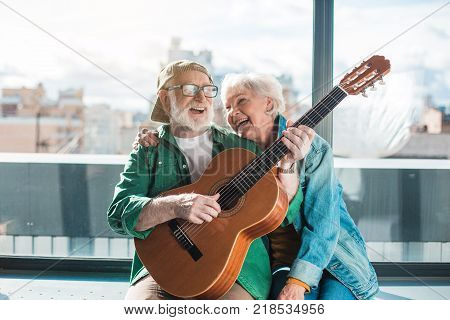 Musical holiday. Waist up portrait of amorous married man and woman enjoying playing on instrument