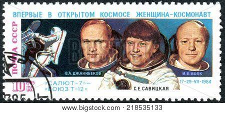 USSR - CIRCA 1985: A stamp printed in the USSR dedicated to the 1st woman's flight in space shows a cosmonauts Vladimir Dzhanibekov Svetlana Savitskaya Igor Volk and Soyuz T-12 Mission circa 1985