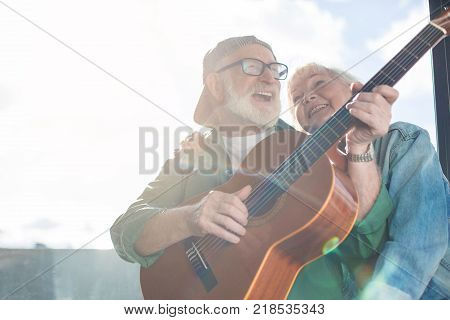 Lovely moment. Low angle portrait of mature charming couple sitting at window while husband is performing favorite song on guitar and wife is tenderly hugging him. Copy space
