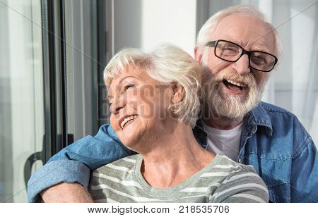 Amusement. Waist up portrait of two happy pensioners hugging each other and expressing gladness and satisfaction