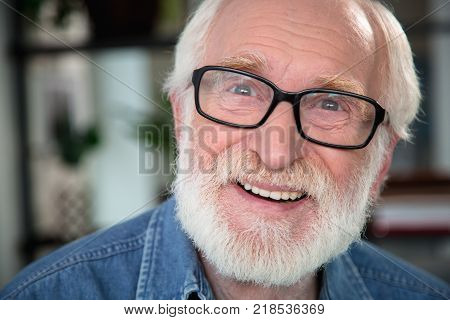Sincere gladness. Close up portrait of happy pensioner expressing delight and openness
