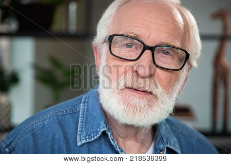 Close up portrait of pensive old bearded man looking at camera. He expresses sincerity, openness while his eye is filled with nostalgia
