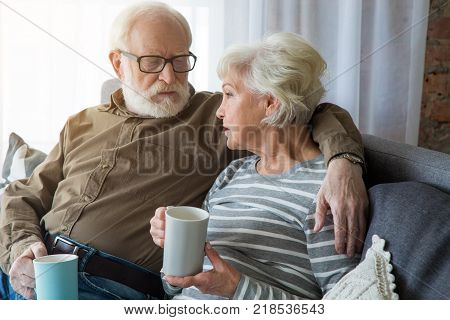 Honest conversation. Portrait of senior couple having dialogue at home while sitting on couch. Husband is cuddling wife while they holding hot cup of tea poster