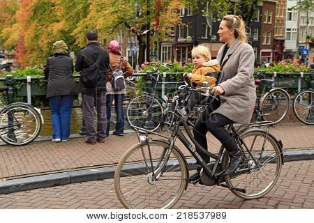 AMSTERDAM/ NETHERLANDS - OCTOBER 25, 2014. A  fashionably dressed woman on a bicycle, carrying her baby in a child seat. Bridge Berensluis over the Prinsengracht canal, Amsterdam, the Netherlands.