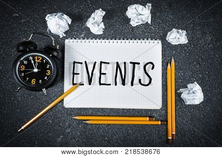 Events word and notebook with pencils crumpled paper balls and clock for event planning concept