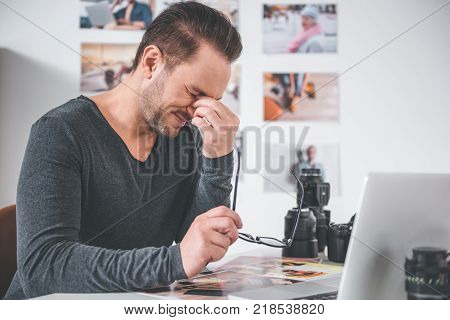 Side view weary unshaven male working at desk in apartment. Fatigue concept