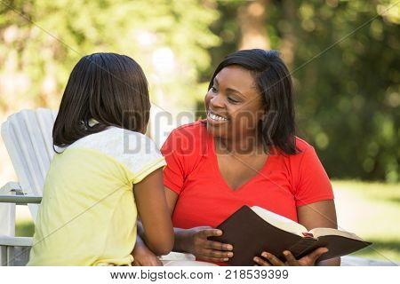 Mother reading wither her daughter outside in the park.