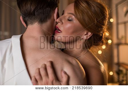 Portrait of ardent red-haired woman hugging man with passion. She is standing and touching male bare shoulder with desire. Her eyes are closed