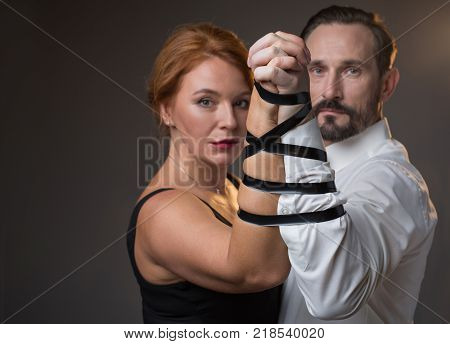 Solemn married couple is connected together forever. They are standing and looking at camera with seriousness. Focus on their hands tied by tape. Isolated