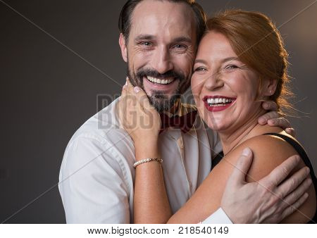 Being loved. Waist up portrait of happy married couple hugging with love and smiling. They are standing and looking at camera with excitement. Isolated