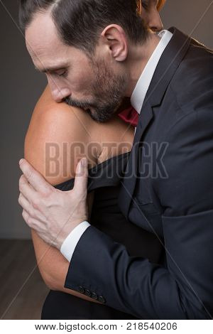 Side view of passionate man kissing woman nude shoulder with desire. Woman is standing in black sexy dress