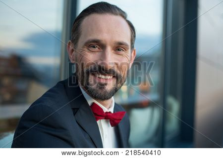 Portrait of happy middle-aged businessman looking at camera and smiling. He is standing in suit and bowtie outdoor