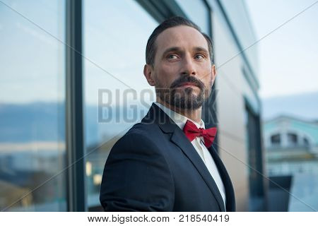 Waist up portrait of confident man in suit standing on balcony. He is looking aside pensively
