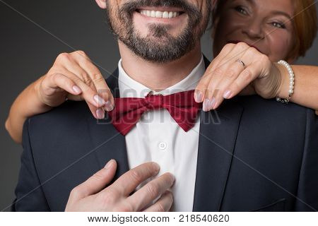 Close up of female hand fixing red bow of male suit. Married couple is smiling