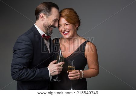 Portrait of cheerful middle-aged lovers are embracing and laughing. They are standing in elegant clothing and holding glasses of champagne. Isolated and copy space