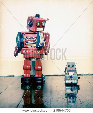 Boss robots looking down on his working robot  on wooden floor with reflection