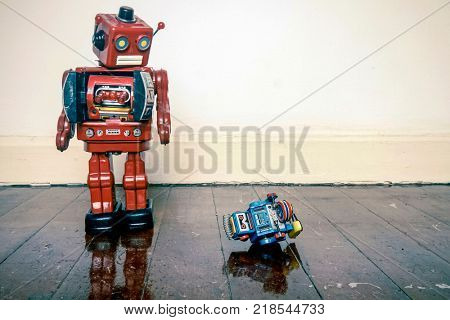 Big retro robot toy humiliates little robot on a wooden floor with reflection