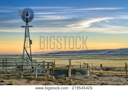 windmill with a pump and cattle water tank, dusk over prairie and foohills of northern Colorado