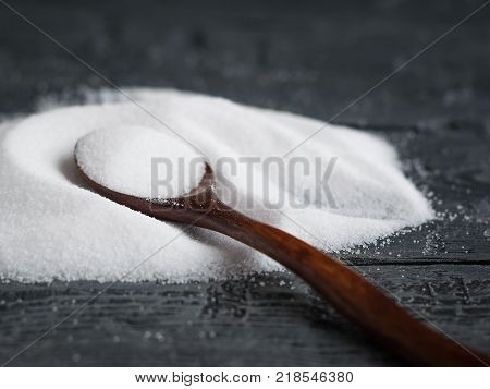 Wooden spoon light wood on a pile of salt finely on a wooden table. Natural sea salt is bright white.