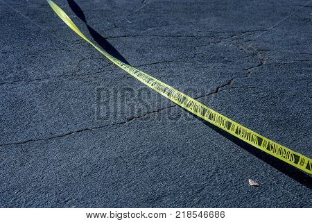 Caution tape in spanish. Yellow tape marked caution in English and cuidado in Spanish on black asphalt.