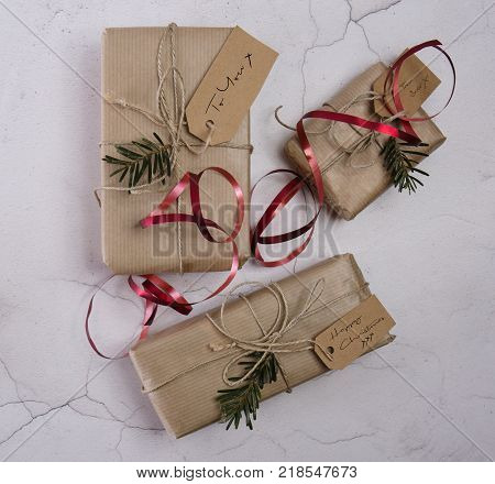 Selection of Christmas presents with lables tied with string and red ribbon