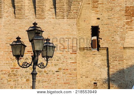 Vintage style lantern before old fortress wall. Spilamberto Italy
