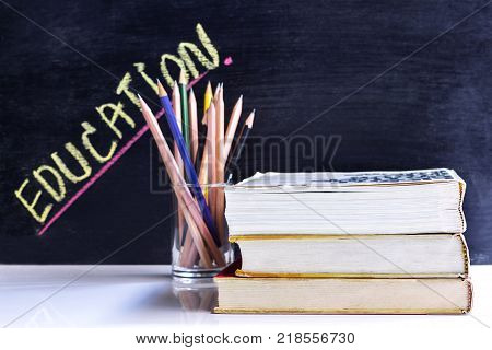 Hardback and textbook stacked with pencils on the table on the blackboard background. The concept of intelligence comes from education. focused on the textbook poster