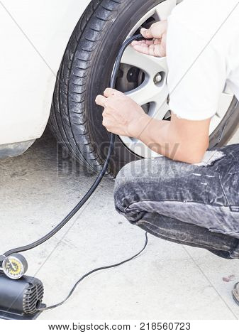 man put on air pump jack to wheel for checking tire pressure safety concept