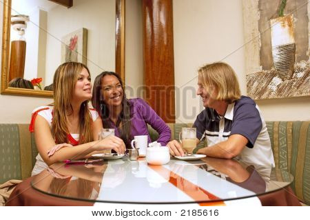 Two Mulatto Girls And Blond Man Drink Coffee And Laugh In A Restaurant
