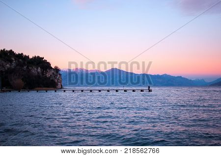 Romantic violet sunset on a lake with a long pier and people walking on it