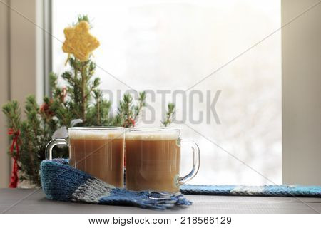 two glass glasses with frothy cappuccino on the background of festive Christmas tree by the window / winter coffee break
