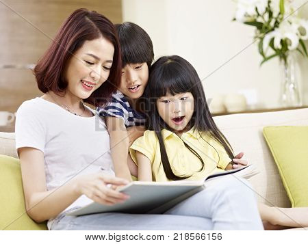 young asian mother sitting on couch at home reading story to two little children.