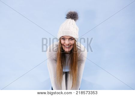 Attractive woman in winter cap and gray sports thermolinen underwear for skiing training studio shot on blue. Long sleeves top and leggings