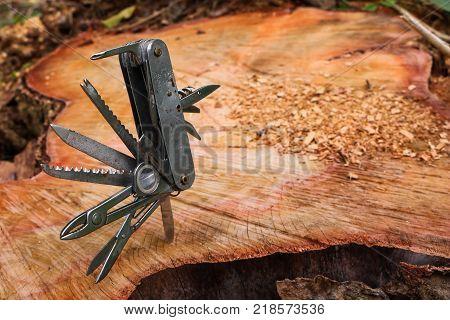 Multifunction knife stuck on the tree stump in the garden