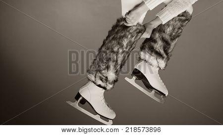 Woman legs wearing skates fur warm socks. Girl getting ready for ice skating. Winter sport activity. Studio shot b&w photo