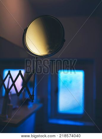 Magnifying Mirror In Dark Eerie Bathroom With Small Window.