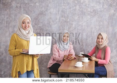 portrait of beautiful muslim woman smiling and standing while holding laptop, her siblings on the back