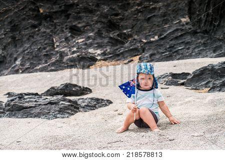 Cute child sitting on the beach with Australian flag on Australia day