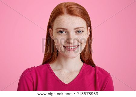 Beautiful ginger female with pleasant smile has freckled skin being glad to be photographed dress in pink sweater isolated over studio background. Red haired pretty young woman poses indoor