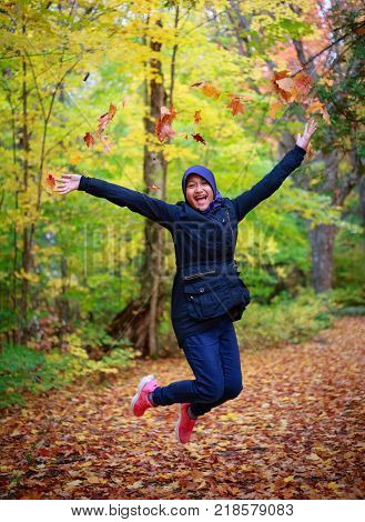 Asian teenager jumping with colorful yellow trees during autumn season