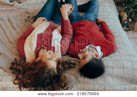 Young attractive couple lays on the bed, looking to each other spending time together. Top view. Young couple laying on the bed smiling with heads upside down.