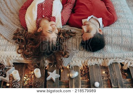 Young couple laying on the bed smiling with heads upside down. Young attractive couple lays on the bed, looking to each other spending time together. Top view poster